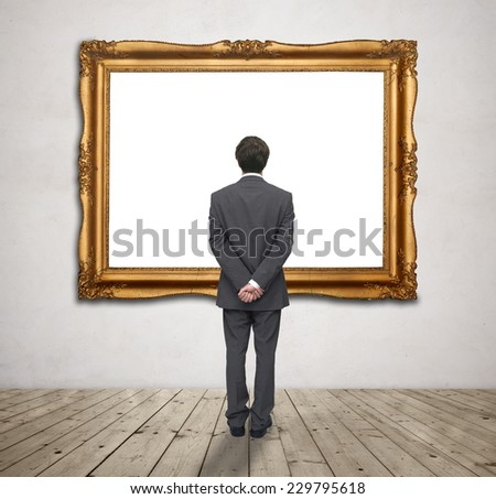 young businessman looking at blank gold frame - stock photo