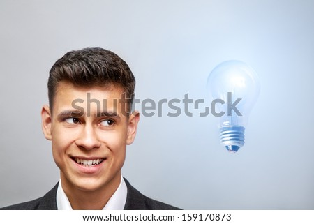Young businessman looking at bulb light over blue background