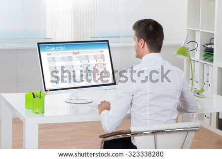 Young Businessman Looking At Calendar On Computer At Desk - stock photo