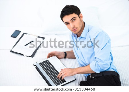 Young businessman looking at camera and using laptop while lying on big white bed in cozy hotel room. Documents and phone are near him