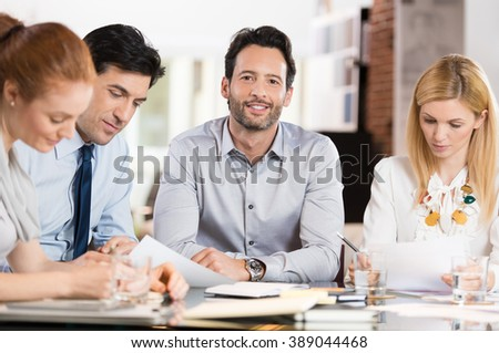 Young businessman looking at camera with colleagues in office. Portrait of proud smiling business man sitting with his colleagues during a meeting. Smiling businessman with executives working. - stock photo