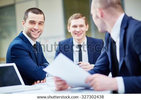 Young businessman looking at camera with his colleagues working near by - stock photo