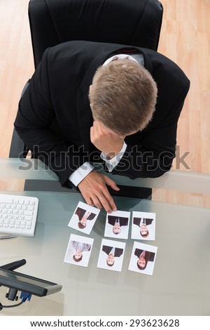 Young Businessman Looking At Candidates Photograph At Desk In Office - stock photo