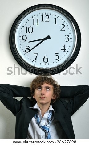 Young businessman looking at clock, deadline concept