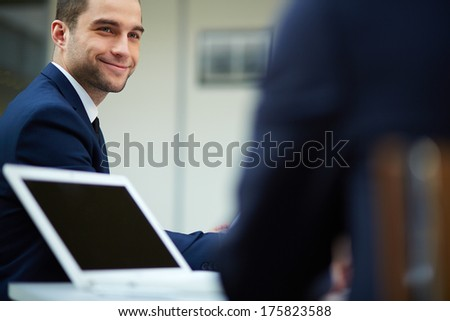 Young businessman looking at colleague at meeting - stock photo