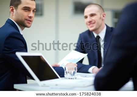 Young businessman looking at colleague during work planning at meeting - stock photo