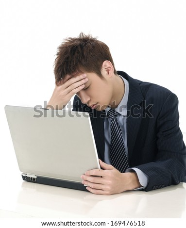 Young businessman looking at computer in desperation
