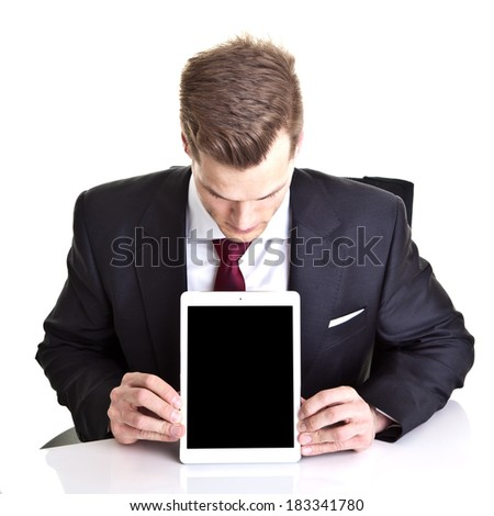 Young businessman looking at empty space on his modern tablet computer - much room for own text - stock photo