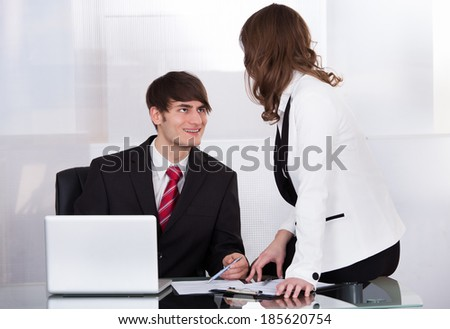 Young businessman looking at female colleague while smiling at desk in office