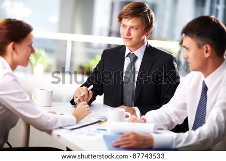 Young businessman looking at female during interview or negotiations - stock photo
