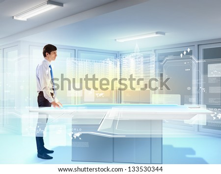 young businessman looking at high-tech image of building model - stock photo
