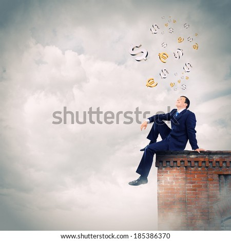 Young businessman looking at money currency signs - stock photo