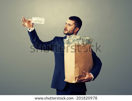 young businessman looking at one hundred dollars and holding paper bag with money. photo in studio over dark background - stock photo