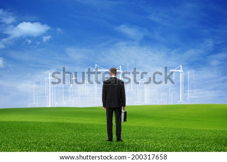 Young businessman looking  at the future project, tower cranes on the background - stock photo