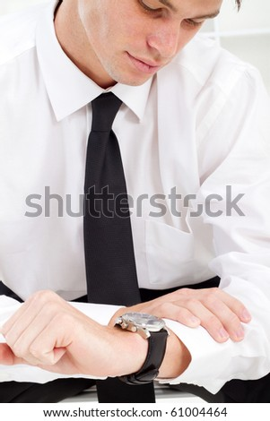 young businessman looking at watch - stock photo