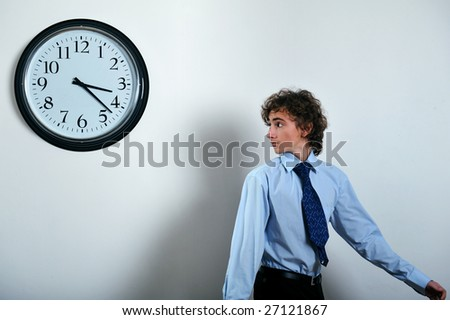 Young businessman looking back at clock, deadline concept - stock photo