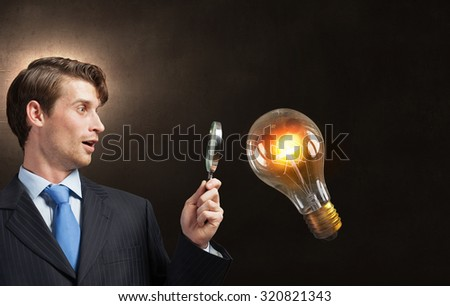 Young businessman looking in magnifying glass at glass light bulb