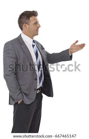 Young businessman looking left, gesturing, talking.