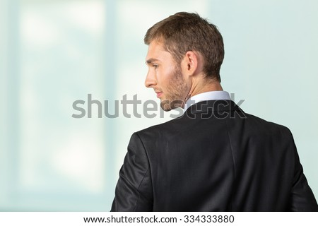 Young Businessman looking over his shoulder - stock photo