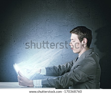 Young businessman looking seriously in tablet pc