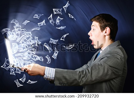 Young businessman looking shocked in laptop monitor - stock photo