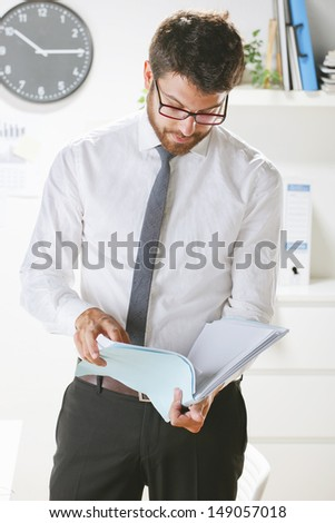 Young businessman looking some papers in office. Businessman with rimmed glasses working.