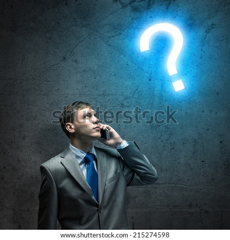 Young businessman looking thoughtfully at question mark - stock photo