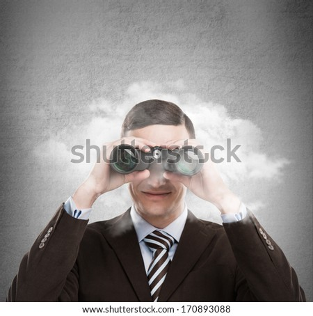 Young businessman looking through binoculars - market research concept - stock photo