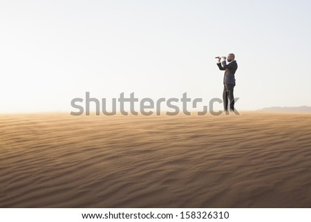Young businessman looking through telescope in the middle of desert - stock photo