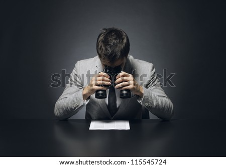 Young businessman looking to a document through a binoculars - stock photo