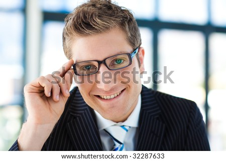 Young businessman looking to the camera wearing glasses