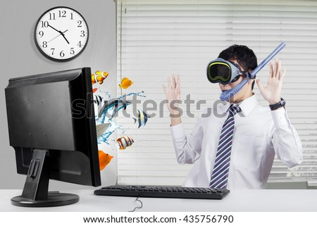 Young businessman looks shocked with fishes coming out from the monitor, wearing goggles and snorkel in the office - stock photo