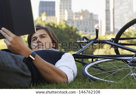 Young businessman lying down on bicycle while reading book in park - stock photo