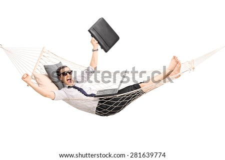 Young businessman lying in a hammock with a laptop in his lap and gesturing joy isolated on white background - stock photo
