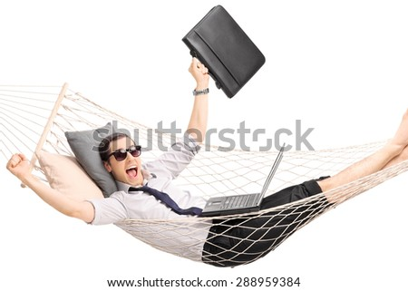 Young businessman lying in a hammock with a laptop in his lap and gesturing joy isolated on white - stock photo