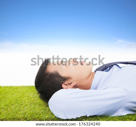 young businessman lying on a meadow and contemplating - stock photo