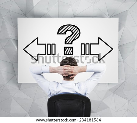 Young businessman making a decision. Arrows and question mark above his head.  - stock photo