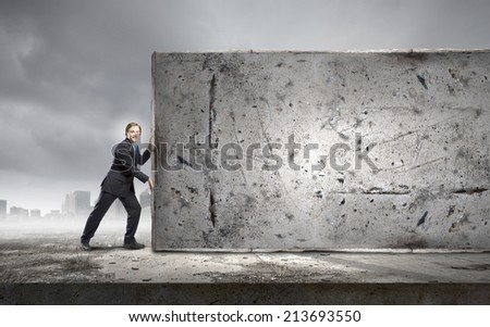 Young businessman making effort to move brick wall