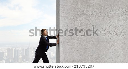 Young businessman making effort to move stone wall