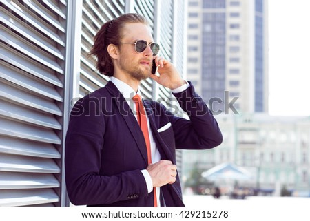 Young businessman, male professional banker in suit talking on mobile phone during work break outdoors, carier start
