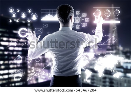 Young businessman managing business charts on illuminated night city background. Management concept