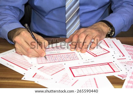 Young businessman Marking on lottery ticket with a pen - stock photo