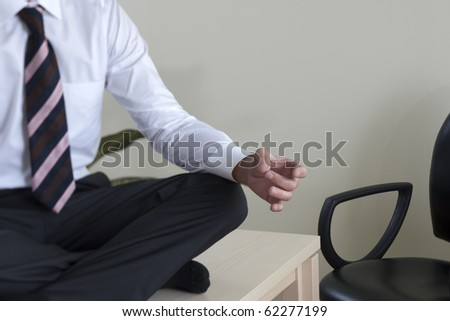Young businessman meditating on his desk