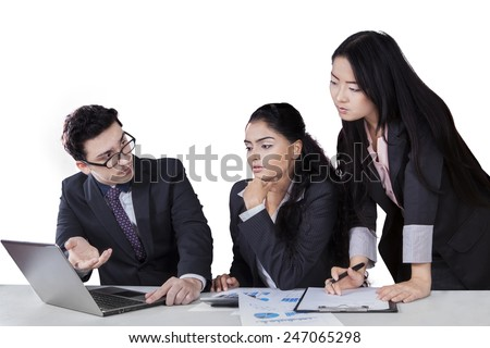Young businessman meet with his partners and explain business plan with laptop computer - stock photo