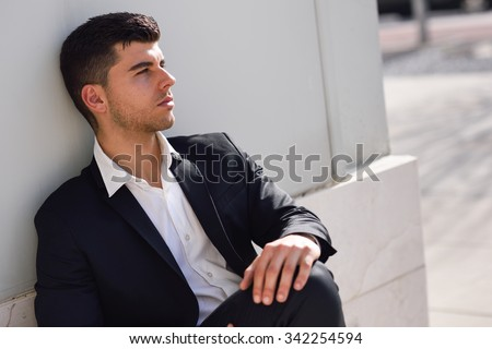 Young businessman near a modern office building wearing black suit and white shirt sitting on the floor. Man with blue eyes in urban background - stock photo