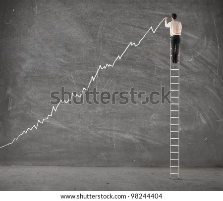 Young businessman on a ladder charting a positive trend graph