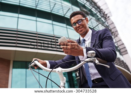 Young businessman on bicycle reading sms in urban environment
