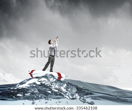Young businessman on floating in water buoy playing pipe - stock photo