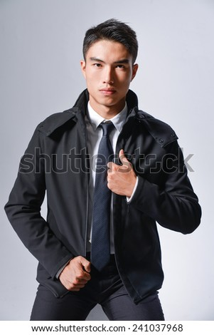 young businessman on gray background, looking at you.