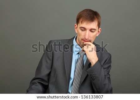 Young businessman on grey background
